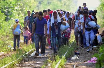 A migrant group walks between the railroad tracks near Roszke village of the Hungarian-Serbian border on August 27, 2015. AFP PHOTO / ATTILA KISBENEDEK